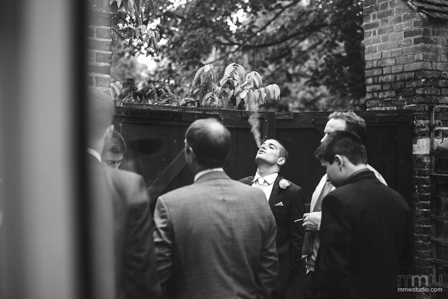 groom and guests smoking cigarettes portrait