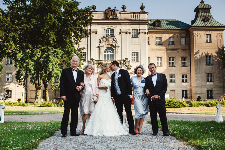 bride and groom with parents at the wedding at rydzyna castle