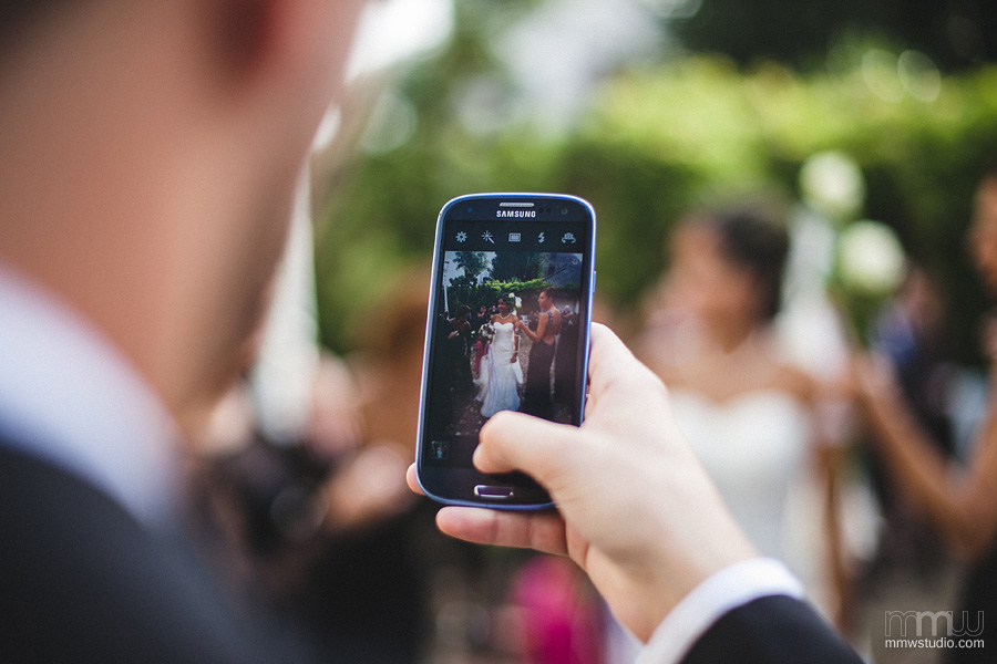 Mobile Phone Wedding Photographers Capturing Bride In Front Of Venue